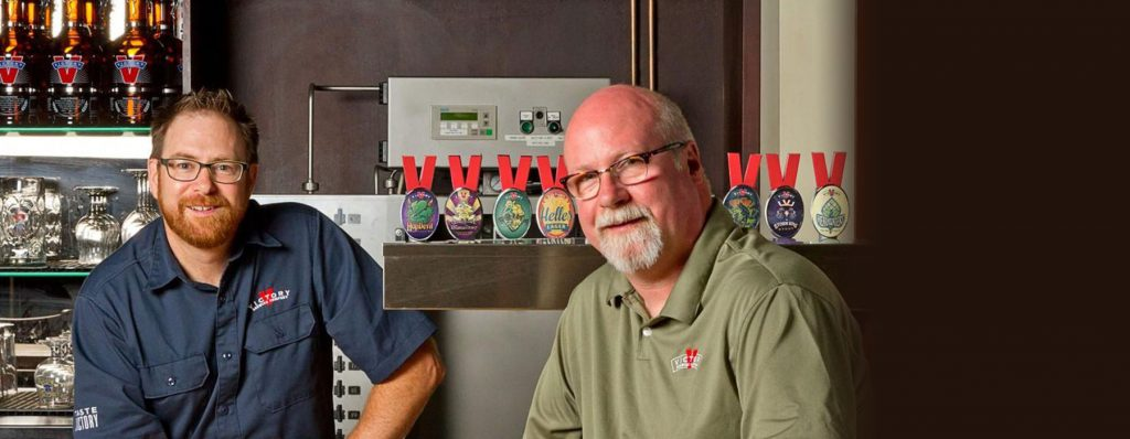 Owners of Victory Brewing stand beside beer taps