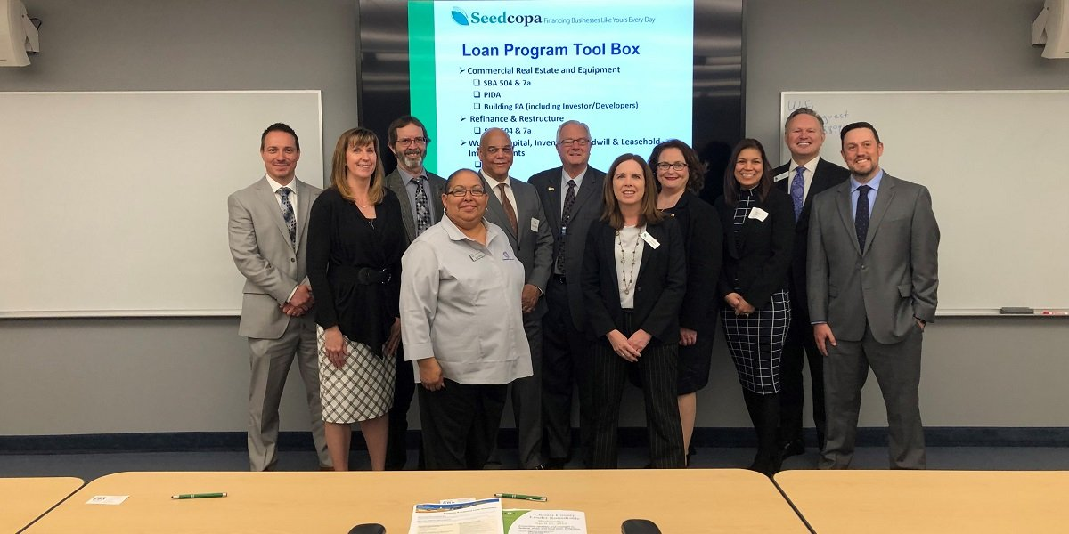 Marie Shires And Sherwood Robbins Stand With Attendees Of Chester County SBA Lender Roundtable