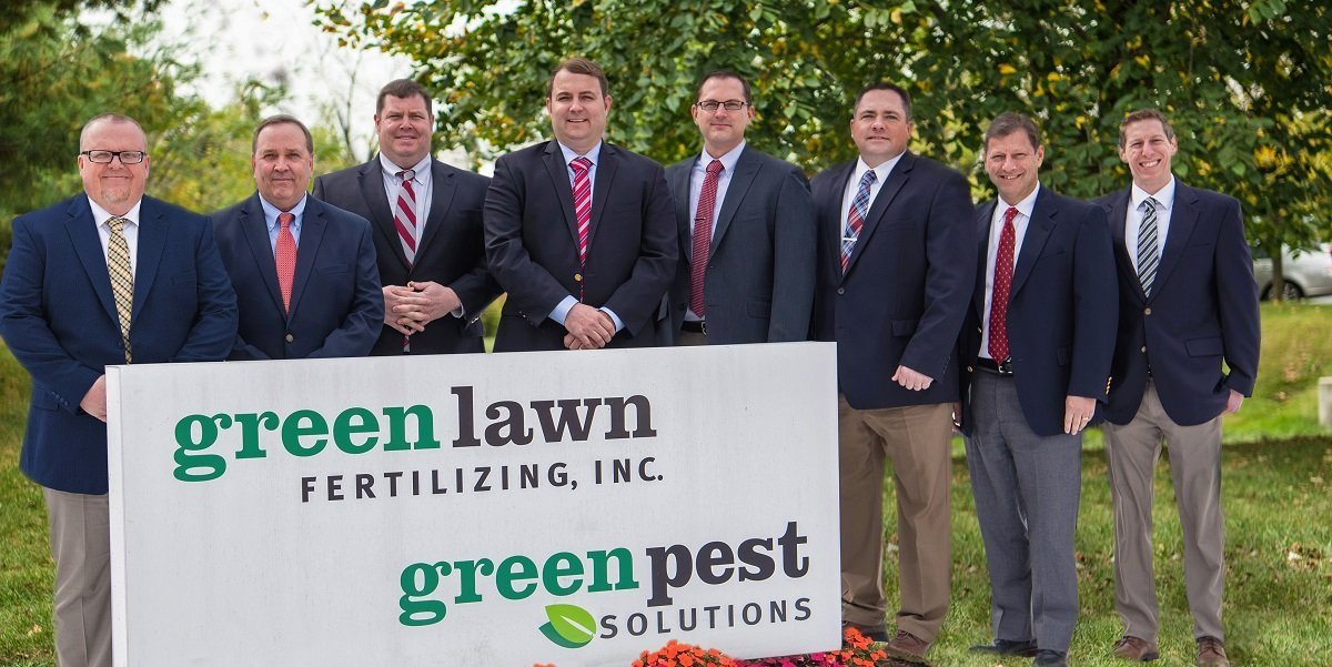 Green Lawn Fertilizing employees stand behind sign