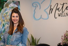 Owner smiles by front desk at Maternal Wellness Center