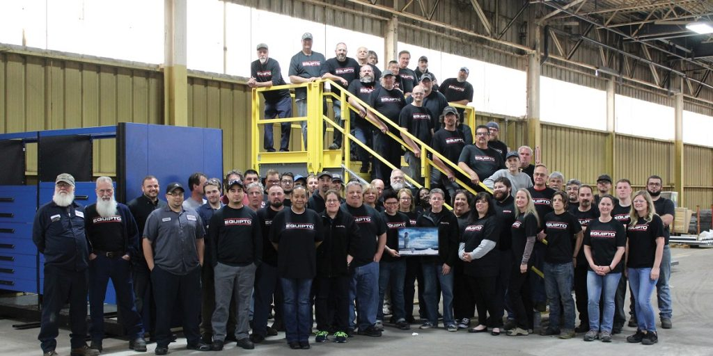 Employees at Consolidated Storage Companies pose next to crossover platform